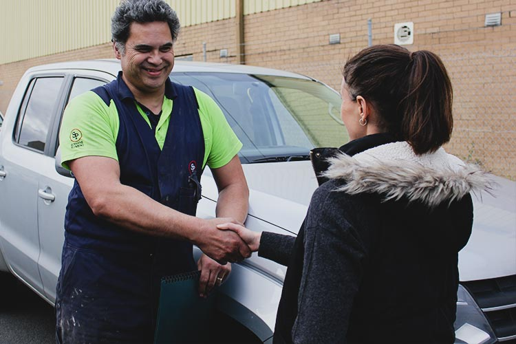 Sunshine Plumbing staff member shaking hands with person